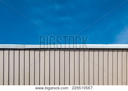 Half Wall Half Blue Sky . Top Part Of The Picture Is Blue Sky, Bottom Part Is Pink Wall With Patern