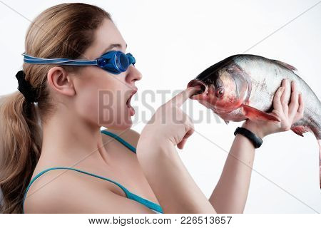 The Girl Looks At The Fish, Holding It In Her Left Hand And Tries To Shove A Finger In Her Mouth Iso