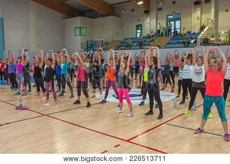 Jozefow, Poland - December 04, 2016:  Group Of Women In Colorful Cloths In A Gym Doing Stretching Ex