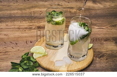 Summer Drink Mojito, Mohito With Mint, Ice And Lime, In Glasses, On A Wooden Table, Macro Photograph