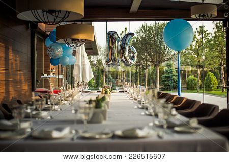 Festively Served Table For The 16th Anniversary. Two Figures 1 And 6 On The Background Of A Table Wi