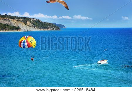 Spectacular Scenic View On Picturesque Bay With People Flying On A Colorful Parachute Towed By A Mot