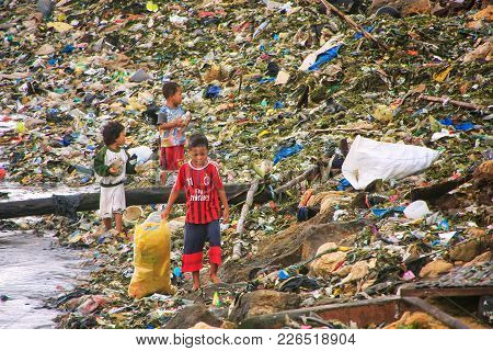 Labuan Bajo, Indonesia-march 17: Unidentified Boys Go Through Garbage At Sea Coast On March 17,2012