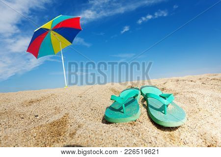 Tropical Background With Flip Flops And Sun Umbrella On The Sandy Beach