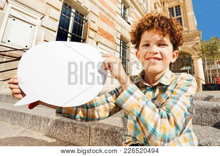 Close-up Portrait Of Cute Curly Teenage Boy Sitting On The Steps Outdoors With White Blanked Speech