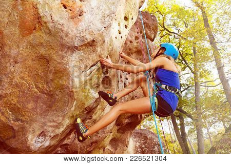 Side View Portrait Of Woman Rock Climbing With Harness In Forest Area
