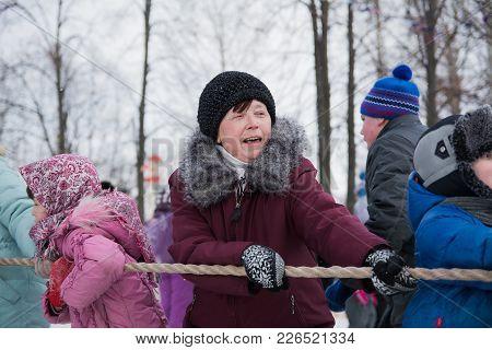 Yoshkar-ola, Russia - February 26, 2016 Tug Of War During The Carnival. Emotional Portrait Of A Woma