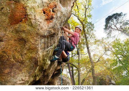 Young Girl Climbs A Rock With Harness In Woodland At Sunny Day