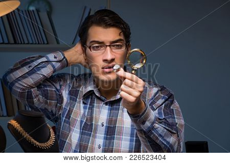 Young male jeweller working at night in his workshop
