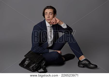 Young Modern Businessman, Dressed In White Shirt And Dark Blue Suit Sitting Crossed Legs Holding Chi