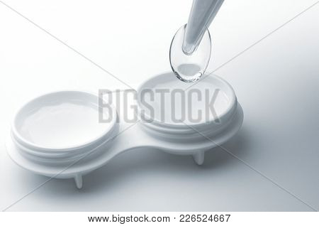 Contact Lens, Case And Tweezers On Grey Background.