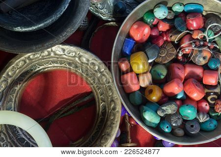 Tibetan Ancient Jewelry: Coral Beads, Turquoise And Amber In A Bowl, Metal Bracelets On A Red Backgr