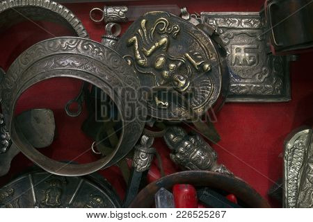 Ancient Buddhist Jewelry, Antique Bracelets From Metal, Pendants With Buddha Image On A Red Backgrou