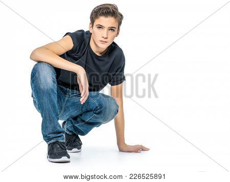 Photo of teenage handsome guy posing at studio. Fashion portrait of cute pretty teen boy