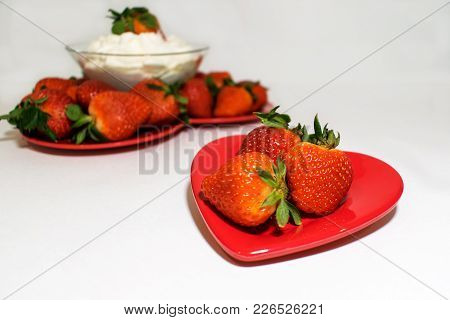 One Small Heart Plate With Strawberries Is In Front Of A Large Heart Plate Filled Also With Strawber