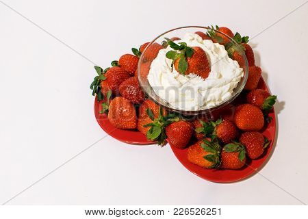 Heart Shape Plate Is Filled With Ripe Strawberries And A Bowl Of Whipped Cream