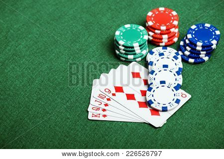 casino chips and cards on a green felt as background