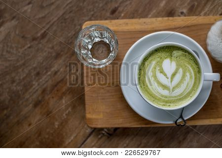 Hot Matcha Green Tea Latte In White Cup On Wood Plate With Some Water In Glass On Wooden Table With
