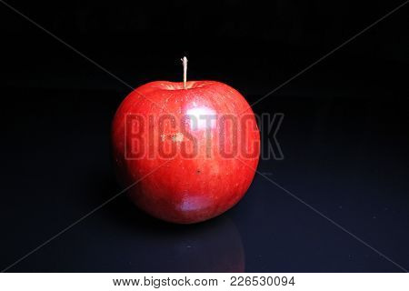 Red Shiny Whole Apple On Black Reflective Studio Background. Isolated Black Shiny Mirror Mirrored Ba