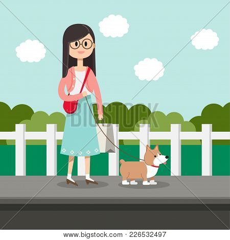 Female Is Walking With Corgi Dog In The Garden