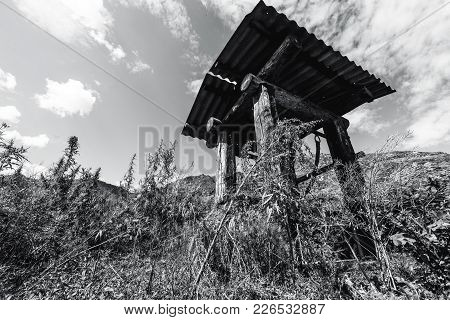 Wide-angle Black And White Shooting Of Wooden Shaft Well In Mountains Surrounded By Cannabis And Wor