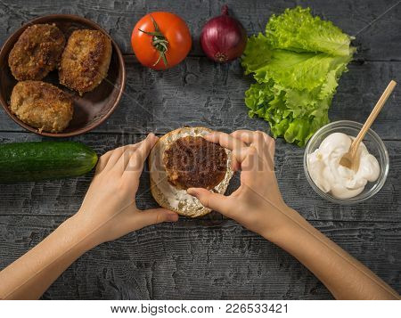 The Girl Puts The Cutlet On A Bun With Sauce For Cooking Hamburger. Cooking Hamburger For School Lun
