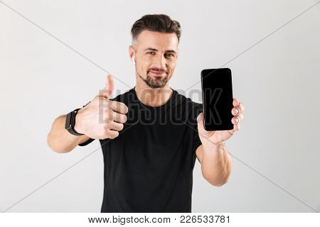 Portrait of a happy mature sportsman showing blank screen mobile phone and showing thumbs up isolated over gray background