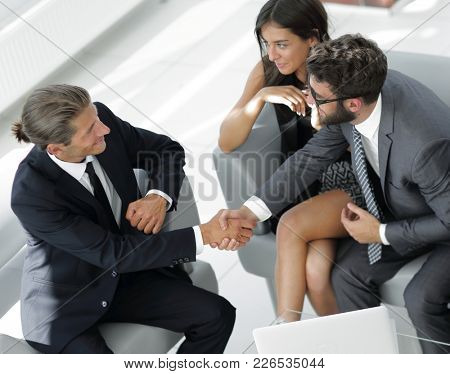 handshake Manager and the client sitting in the office lobby.