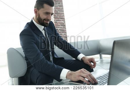 businessman working on laptop sitting in office lobby