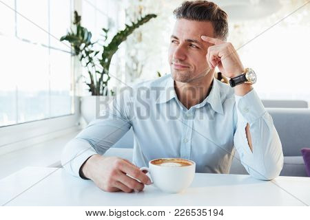 Photo of masculine man 30s sitting alone in city cafe with cup of coffee beverage and looking aside in window with brooding sight