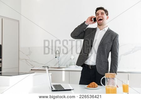 Portrait of positive man in businesslike clothes laughing out loud while speaking on mobile phone on lunch time at home