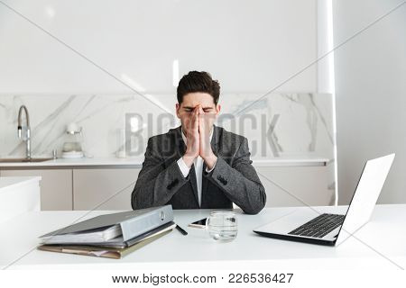 Portrait of tired businessman covering his face with hands while overworking and sitting at table in office with closed eyes
