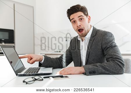 Photo of executive male employer pointing finger on screen of laptop in surprise while doing freelance work from home