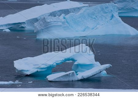 A Blue, Arched Iceberg In Charlotte Bay, Antarctica.