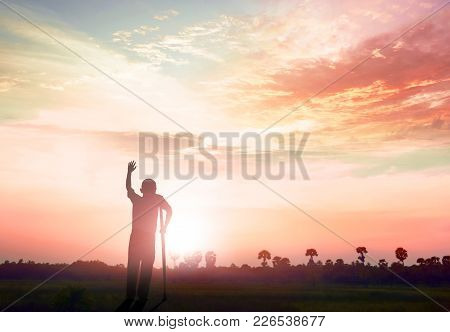 Healing  Concept: Silhouette A Disabled Man Standing Up At Mountain Sunset Background