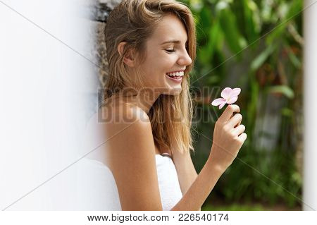 Sideways Portrait Of Smiling Beautiful Female Holds Small Flower, Wears Towel, Stands Against Tropic