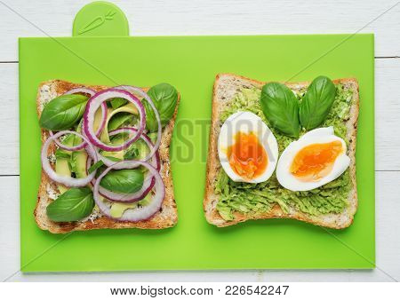 Two Avocado Toasts With Soft Boiled Eggs,mashed Avocado,sliced Avocado ,red Onion,basil Leaves And G