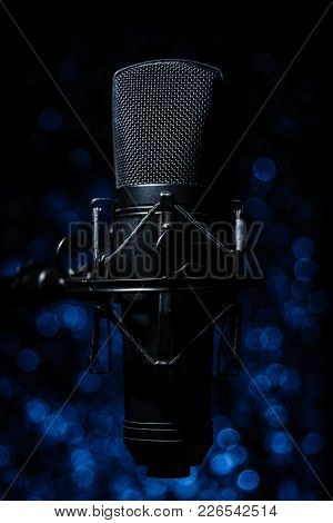 Black Vocal Microphone With Blue Background Bokeh