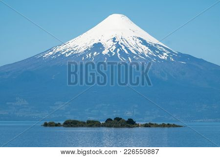 Volcano of Osorno during sunny day with island on the foreground. Chile