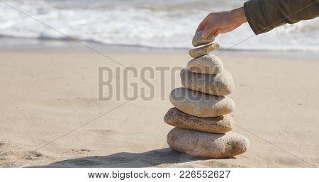 Hand putting the pebble stone on balance zen stock