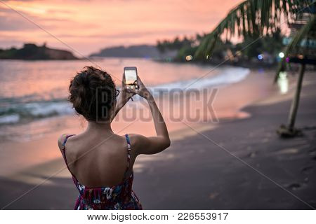 Charming Girl In Glasses Makes A Photo Of The Sunset Sky Beach Landscape On Her Cellphone On Sri Lan