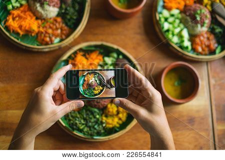 Vegetarian Indian Cuisine. The Man Takes A Photo On His Smartphone Dishes With Rice, Ogriks, Spinach