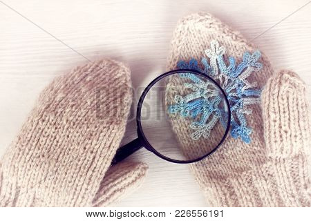 Lying On A Mitten A Blue Snowflake Is Viewed In A Magnifying Glass / Winter Which Is Knitted From A
