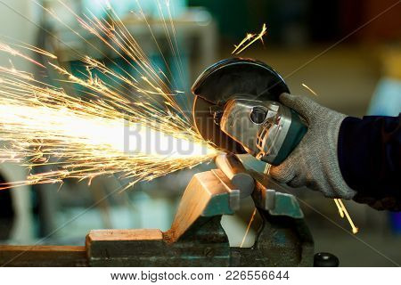 A Man Working With Hand Tools. Hands And Sparks Close-up. Production Of Parts. Angular Grinding Mach