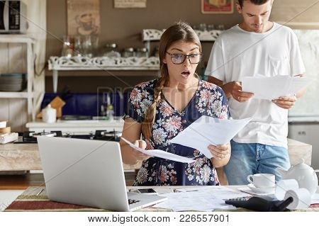 Young Female Looks With Shocked Expression Into Papers, Recieve High Taxes And Had To Pay Much Money