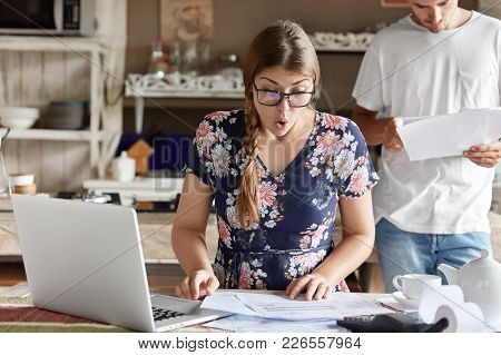 Indoor Shot Of Shocked Woman In Blouse, Looks With Puzzled Expression Into Documents, Makes Financia