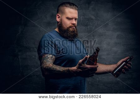 Studio Portrait Of Brutal Bearded Hipster Male With Tattoo On Arm, Looking At Two Beer Bottles On Gr