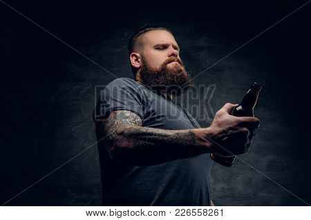 Studio Portrait Of Brutal Bearded Hipster Male With Tattoo On Arm, Looking At The Beer Bottle On Gre