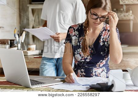 Concerned Young Female In Eyewear, Can`t Understand How Make Financial Report, Sits At Kitchen Table