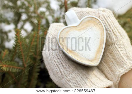 Foamy Hot Cappuccino In The Shape Of A Heart In The Hands Dressed In Knitted Mittens Against The Bac